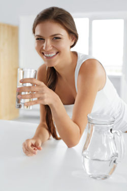 47895069 - beauty, diet concept. happy smiling woman drinking fresh crystal clear water from a glass. healthcare. healthy lifestyle and eating. health, dieting, fitness concept. drinks