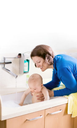 56545239 - mother washing her baby in a hospital room. mom bathing little boy during clinic stay at children station. health care and for young kids. parent and child stay in room. infant recovery after sickness